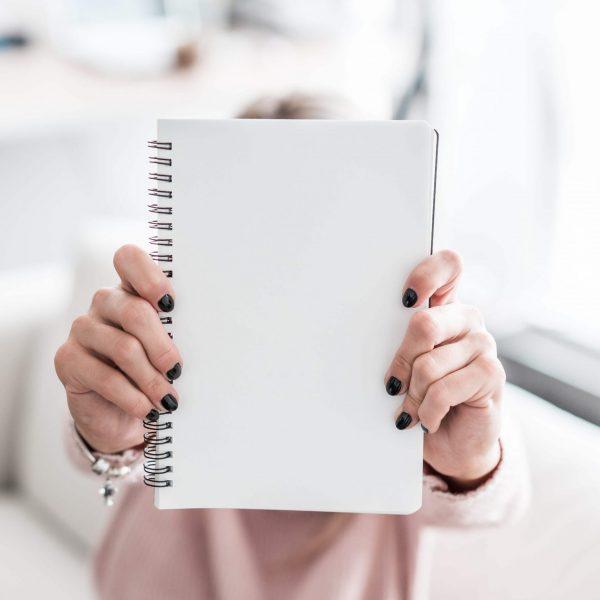woman-holding-blank-notebook-picjumbo-com